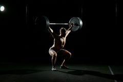 Fitness training. Man doing sit ups with barbell. Fitness training. Man doing sit ups exercise with barbell in dark gym Stock Image
