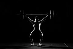 Fitness training. Man doing sit ups with barbell. Fitness training. Man doing sit ups exercise with barbell in dark gym Royalty Free Stock Images