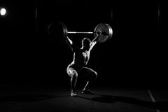 Fitness training. Man doing sit ups with barbell. Fitness training. Man doing sit ups exercise with barbell in dark gym Stock Photos