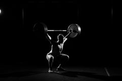 Fitness training. Man doing sit ups with barbell. Fitness training. Man doing sit ups exercise with barbell in dark gym Royalty Free Stock Image