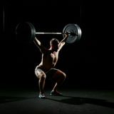 Fitness training. Man doing sit ups with barbell. Fitness training. Man doing sit ups exercise with barbell in dark gym Royalty Free Stock Photography