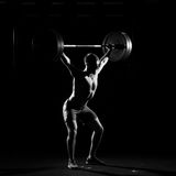 Fitness training. Man doing sit ups with barbell Royalty Free Stock Photo