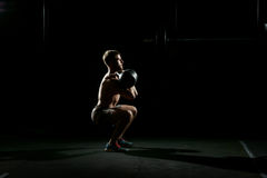 Fitness training. Man doing sit ups with weights. In dark gym Royalty Free Stock Image
