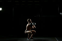 Fitness training. Man doing sit ups with weights. In dark gym Royalty Free Stock Photos