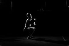 Fitness training. Man doing sit ups with weights. In dark gym Royalty Free Stock Photography