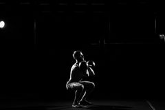 Fitness training. Man doing sit ups with weights. In dark gym Stock Photography