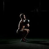 Fitness training. Man doing sit ups with weights Stock Photos