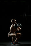 Fitness training. Man doing sit ups with weights. In dark gym Royalty Free Stock Photo