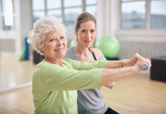 Fitness training with a personal trainer at gym. Senior women exercising with fitness trainer at gym. Active senior women lifting dumbbells with help from Royalty Free Stock Photos