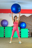 Fitness training. Young beautiful white girl in a pink sports suit does physical exercises with a blue fit ball. Royalty Free Stock Photos