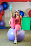 Fitness training. Young beautiful white girl in a pink sports suit does physical exercises with a violet fit ball. Young beautiful white girl in a pink sports stock image