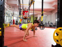 Fitness TRX training exercises at gym woman and man. Crossfit fitness TRX training exercises at gym women push-up and dip rings men workout Royalty Free Stock Photo