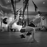 Fitness TRX training exercises at gym woman and man. Fitness TRX training exercises at gym women and men push-up workout Royalty Free Stock Photo