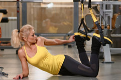 Fitness TRX training exercises at gym woman Stock Photos