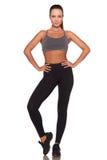 Fitness vrouw in sportstijl die zich tegen geïsoleerde witte achtergrond bevinden stock afbeelding