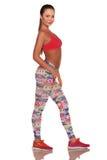 Fitness vrouw in sportstijl die zich tegen geïsoleerde witte achtergrond bevinden stock foto