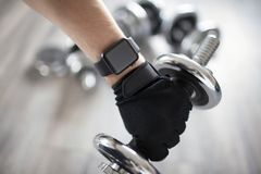 Fitness smart watch on hand. Fitness watch with dumbbells in the background royalty free stock photography
