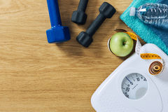 Fitness and weight loss. Concept, dumbbells, tape measure, white scale towels and water bottle on a wooden table, top view Royalty Free Stock Photography