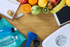 Fitness and weight loss. Concept, dumbbells, white scale, towels, fruit, tape measure and digital tablet on a wooden table, top view Stock Image