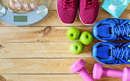 Fitness and weight loss concept, running shoes, dumbbells, tape. Measure, apples, bananas, weighting scale, top view with copy space stock photos
