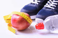 Fitness. Weight loss concept with sneakers, apple & bottle Royalty Free Stock Photo