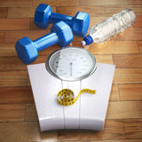 Fitness and weight loss concept. Weigh scales, dumbells and meas Stock Images