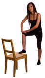 Fitness woman. A young woman exercising using a chair Royalty Free Stock Images