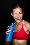 Fitness woman. Smiling with happy fresh energy while sweating and drinking water from bottle. Chinese Asian / white Caucasian female model on black background Royalty Free Stock Photos
