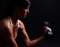Fitness woman. Lifting fee weights set against a dark background Stock Photo