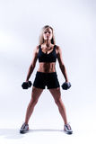 Fitness woman. A young woman working out on a plain backdrop Stock Photography