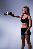 Fitness woman. A young woman working out on a plain backdrop Stock Photo