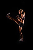 Fitness woman. A young woman working out on a plain backdrop Royalty Free Stock Photos