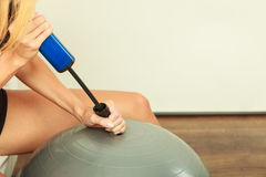 Fitness woman with air pump inflating fit ball Royalty Free Stock Image
