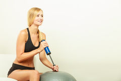 Fitness woman with air pump inflating fit ball Stock Photos