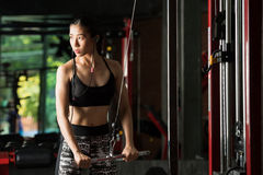 Fitness woman, Asian woman flexing arm muscles on cable machine Stock Photos