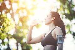 Fitness woman athlete takes a break, Drinking water, Hot day. Co. Untry rural road nature background stock photo
