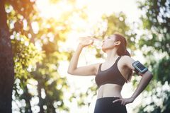 Fitness woman athlete takes a break, Drinking water, Hot day. Co. Untry rural road nature background stock images