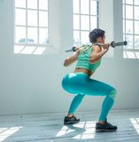 A woman squatting with barbell. Fitness woman from the back in azure sportswear doing squats with barbell on her shoulders stock image