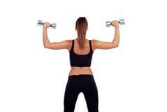 Fitness woman back lifting dumbbells Stock Image