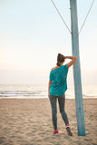 Fitness woman on beach in the evening looking into Royalty Free Stock Photography