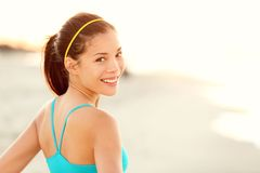 Fitness woman beach portrait. Happy sporty Asian runner resting and smiling after running workout outdoors on sunny summer day Stock Photography