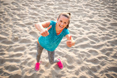 Fitness woman on beach showing thumbs up Royalty Free Stock Photos