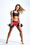 Fitness woman. Beautiful fitness female posing on studio background with barbells Royalty Free Stock Images