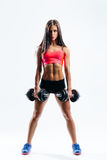 Fitness woman. Beautiful fitness female posing on studio background with barbells Royalty Free Stock Photo