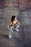 Fitness woman with beautiful figure crouching on concrete background. Sporty woman in colorful leggings with beautiful fitness body against concrete wall Royalty Free Stock Photos