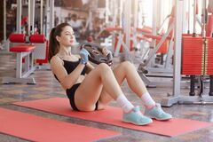 Free Fitness Woman Being Photographed During Her Workout At Gym. Muscular Woman Sitting On Mat On Floor Doing Abs Exercise With Heavy Royalty Free Stock Images - 185810339