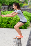 Fitness woman bench jump squat jumping on beach. Fitness woman athlete bench jump squat jumping outside in nature landscape. Strength training fit girl working Royalty Free Stock Image