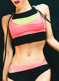 Fitness woman on a black background in bright sportswear Stock Image