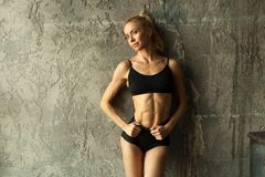 Fitness blondie woman standing near the wall stock photos