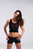 Fitness woman in black tank top and shorts, studio shot. Stock Photography